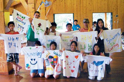아름다운재단이 운영하는 나눔캠프에 참여한 학생들이 자신이 생각하는 나눔의 주제를 표현한 티셔츠를 들고 환하게 웃고 있다. 아이들은 '나누면 행복하다''우린 모두 친구'등의 문구를 써넣었다.