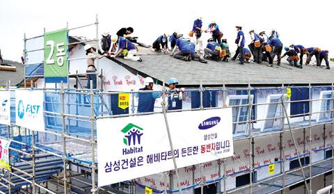 삼성물산 임직원들이 3층 높이의 지붕 위에서 집짓기에 땀을 흘리고 있다. 해비타트운동으로 지어지는 집의 공정 중 60%이상이 이런 자원봉사자들의 힘으로 이루어진다. /삼성물산 제공